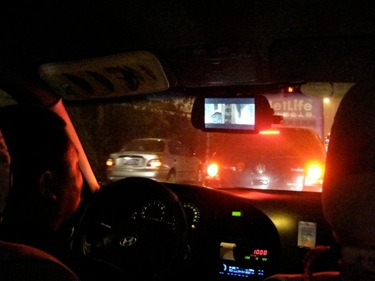 Taxi drivers watches a video player on his rear view mirror